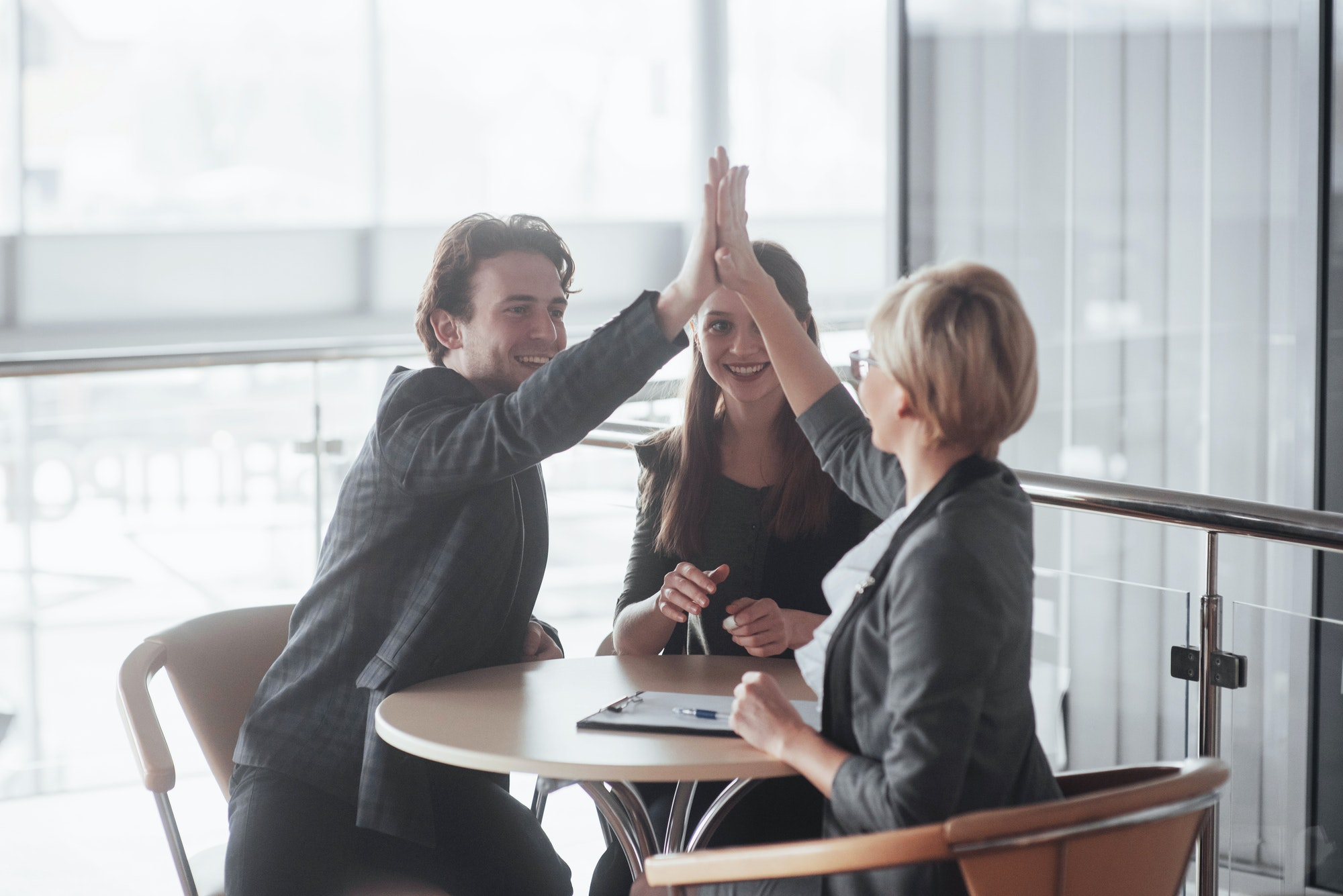 Happy successful business team giving a high fives gesture as they laugh and cheer their success