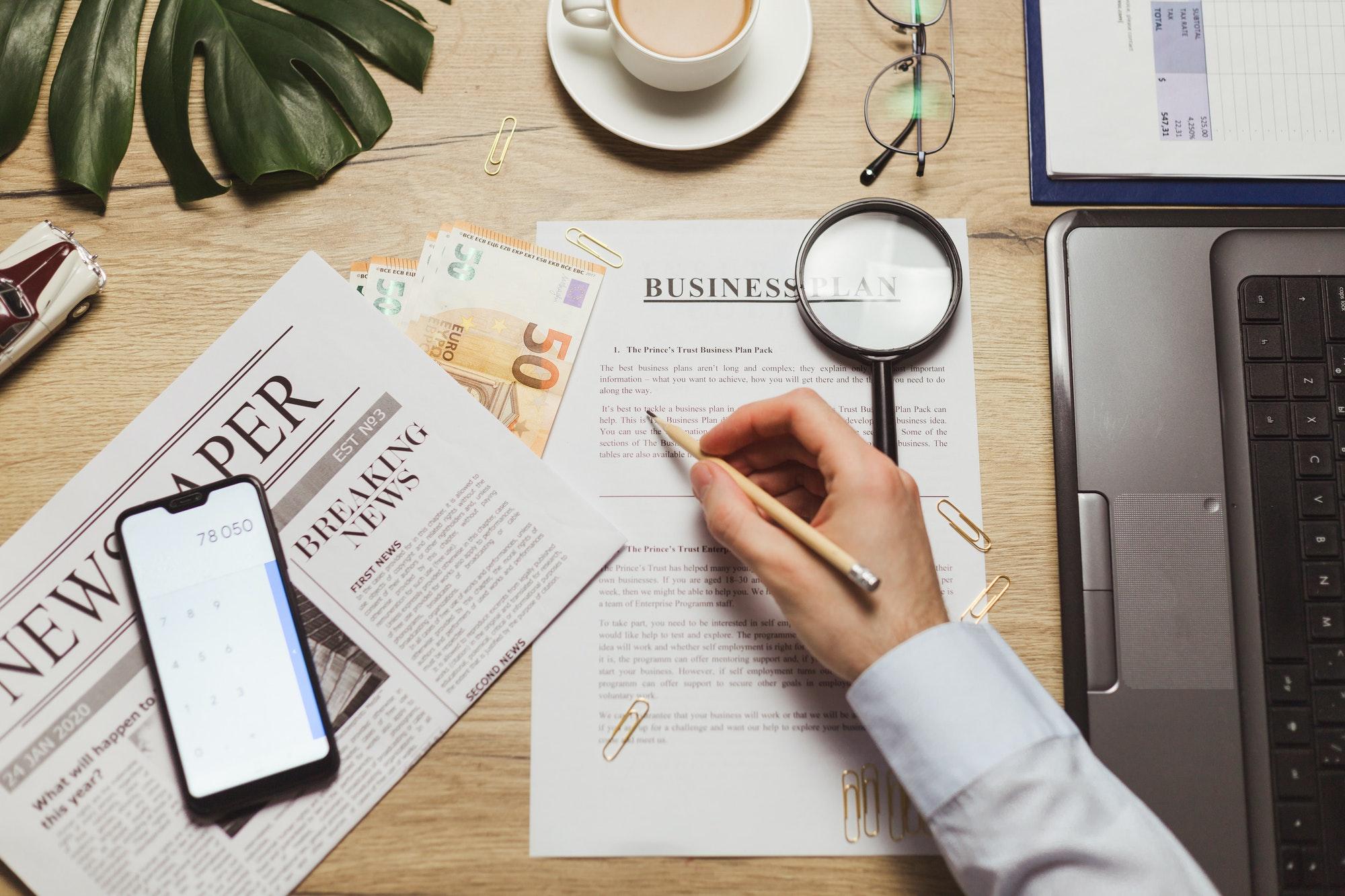 businessman hand checking marketing document business plan